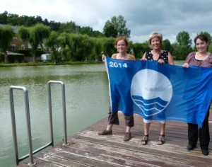 Anne Thibaut (Inter-environnement), Monique Jacob (échevine) et Cécile Zintz (Contrat rivière Semois-Chiers) présentent le Pavillon bleu.